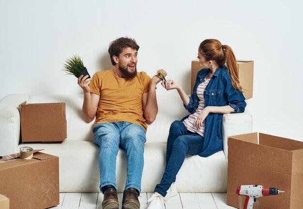 Jeune couple avec des choses dans des boîtes sur le canapé en mouvement de pendaison de crémaillère