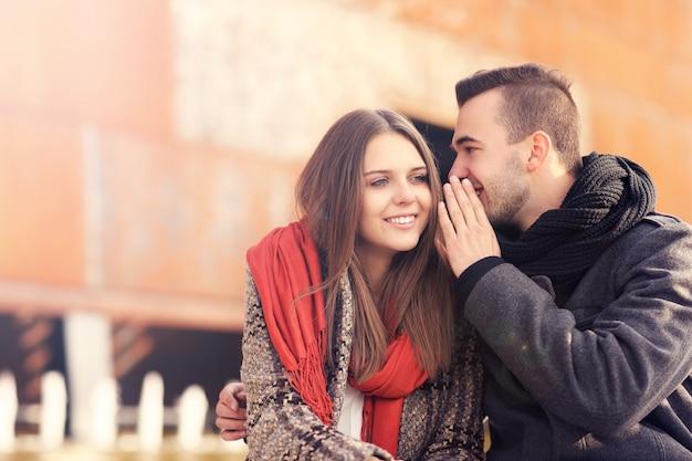 Un jeune couple chuchotant un jour d'automne