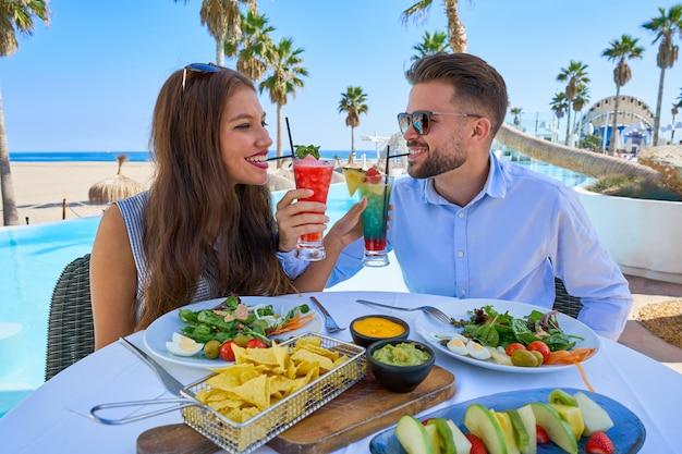 Jeune couple avec cocktails au restaurant de la piscine