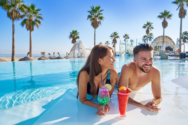 Jeune couple sur les cocktails à la piscine à débordement