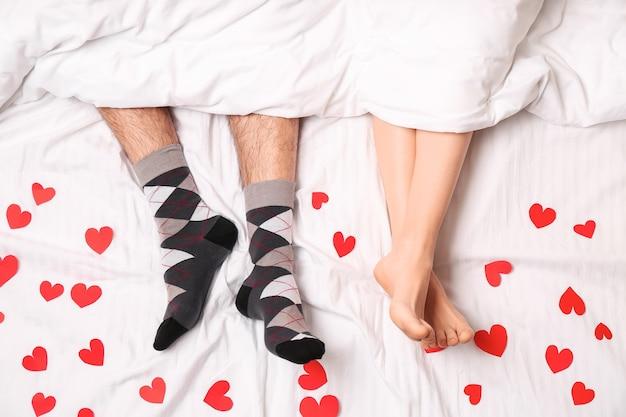 Jeune couple, à, coeurs rouges, situer dans lit, vue dessus