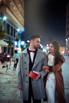 Jeune couple avec des coffrets cadeaux dans la rue