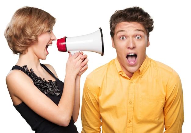 Jeune couple en colère avec mégaphone sur fond