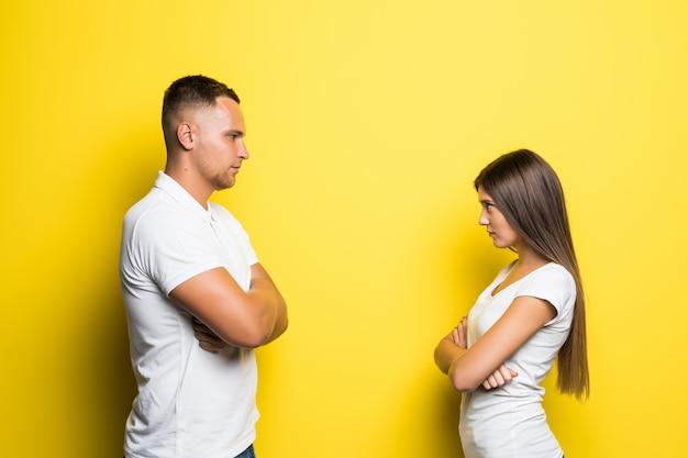 Jeune couple en colère vêtu de t-shirts blancs à la recherche l'un de l'autre sur fond jaune