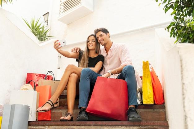 Jeune couple commerçant prenant des selfies
