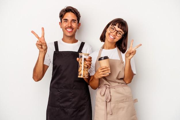 Jeune couple de commis de magasin de race mixte isolé sur fond blanc montrant le numéro deux avec les doigts.