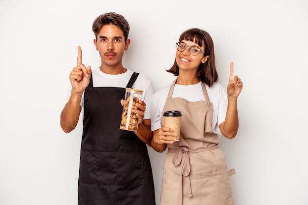 Jeune couple de commis de magasin de race mixte isolé sur fond blanc montrant le numéro un avec le doigt.