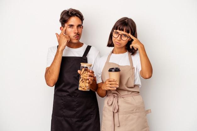Jeune couple de commis de magasin de race mixte isolé sur fond blanc pointant le temple avec le doigt, pensant, concentré sur une tâche.