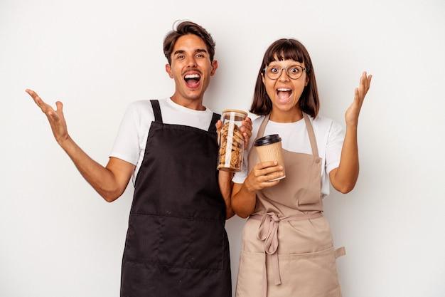 Jeune couple de commis de magasin de race mixte isolé sur fond blanc recevant une agréable surprise, excité et levant les mains.