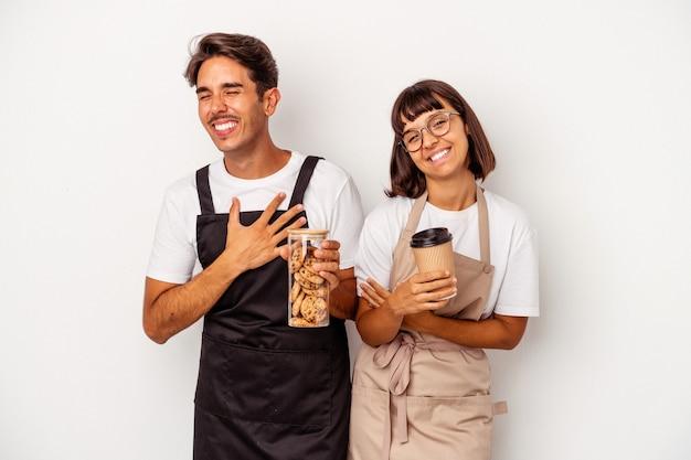 Jeune couple de commis de magasin de race mixte isolé sur fond blanc en riant et en s'amusant.
