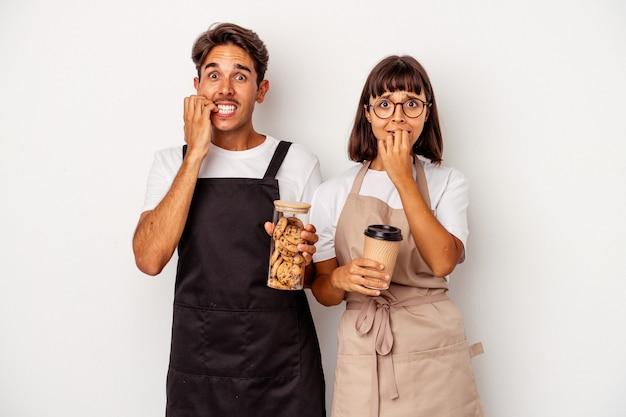 Jeune couple de commis de magasin de race mixte isolé sur fond blanc se ronger les ongles, nerveux et très anxieux.