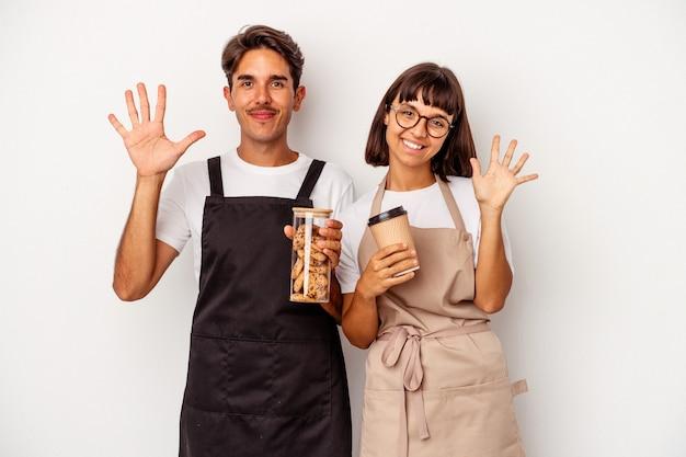 Jeune couple de commis de magasin de race mixte isolé sur fond blanc souriant joyeux montrant le numéro cinq avec les doigts.