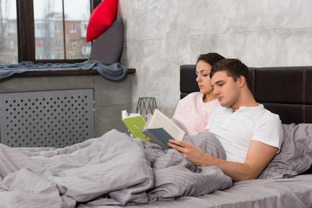 Jeune couple concentré lisant des livres en position couchée dans le lit et portant un pyjama dans la chambre de style loft avec des couleurs grises
