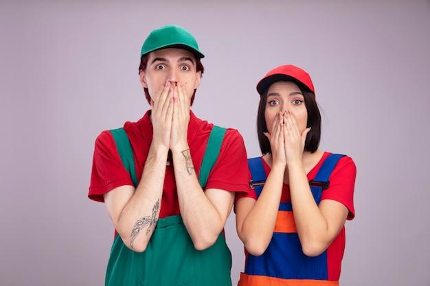 Jeune couple concerné en uniforme de travailleur de la construction et casquette gardant les mains sur la bouche en regardant la caméra isolée sur le mur blanc
