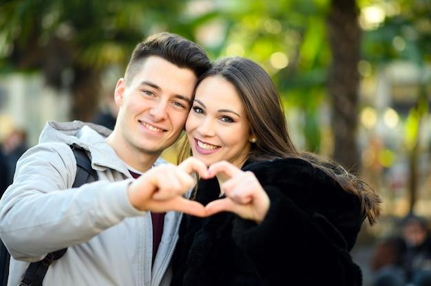Jeune couple, confection, forme coeur, à, leurs mains