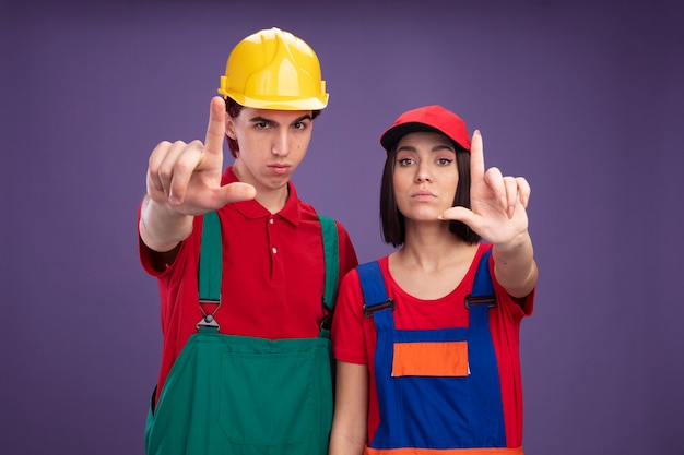 Jeune couple confiant en uniforme de travailleur de la construction portant un casque de sécurité girl wearing cap étendant la main faisant un geste de perdant