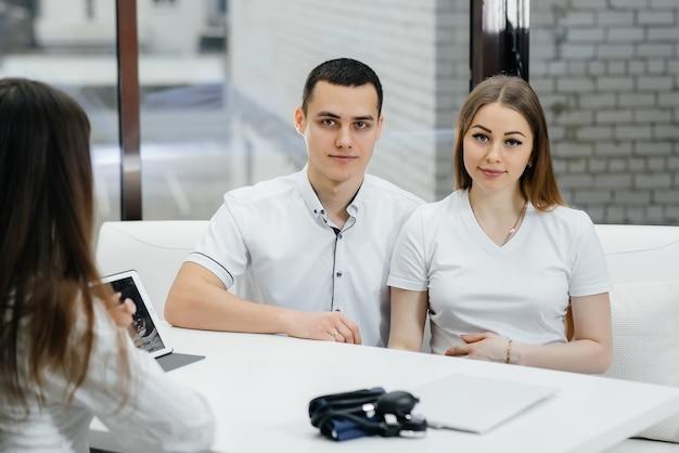 Un jeune couple à la consultation d'un gynécologue après une échographie. grossesse et soins de santé
