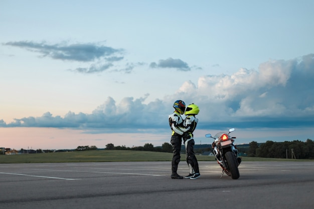 Jeune couple en costume de motard près d'une moto.