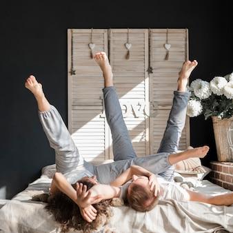 Jeune couple, coucher lit, étirer jambes, chez soi