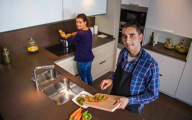 Jeune couple coupant des légumes dans la cuisine pour préparer des aliments