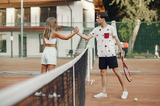 Jeune couple sur un court de tennis. deux joueurs de tennis dans un vêtement de sport.