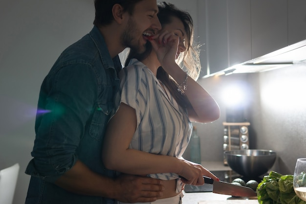 Jeune couple cuisinant un délicieux dîner ensemble dans une cuisine le soir