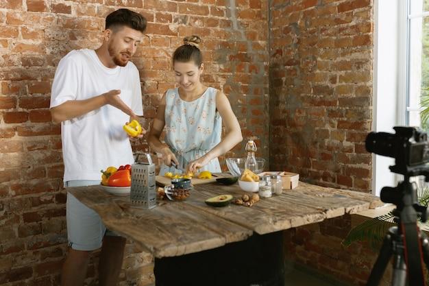 Jeune couple cuisinant et enregistrant une vidéo en direct pour vlog et médias sociaux