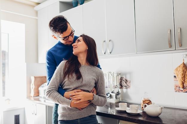 Jeune couple, cuisine, étreindre, boire, thé