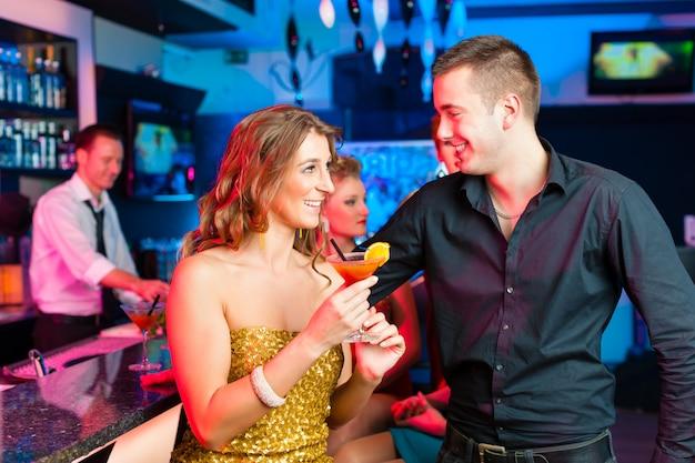 Jeune couple dans un bar ou un club buvant des cocktails