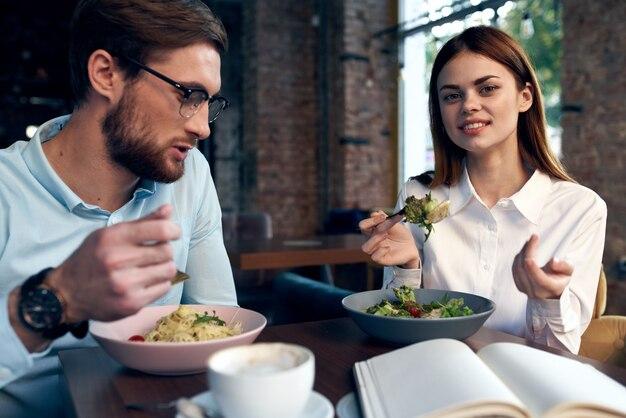 Jeune couple dans un café assis à la table petit déjeuner communication reste