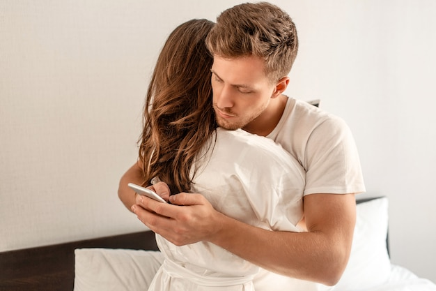 Jeune couple dans la chambre. un homme séduisant vérifie les messages entrants le matin