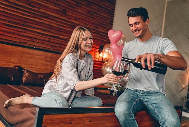 Jeune couple dans la chambre avec des verres et du vin
