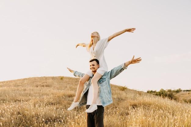Jeune couple dans un champ. homme tenant une femme sur ses épaules, les deux bras grands ouverts.