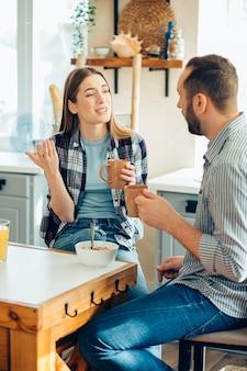 Jeune couple dans la cuisine ayant une conversation intéressante photo stock