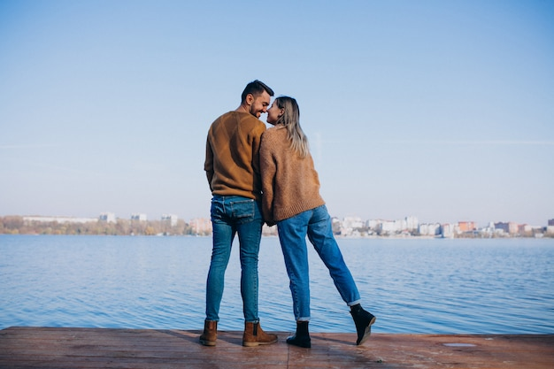 Jeune couple dans un parc debout près de la rivière