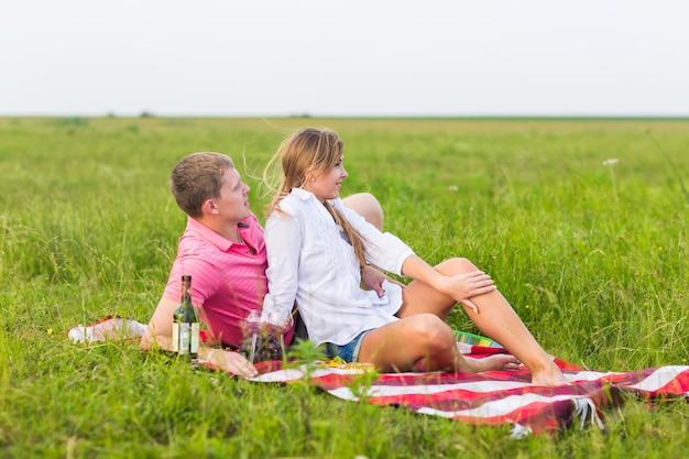 Jeune couple dans la prairie d'été, homme et femme ayant pique-nique romantique.