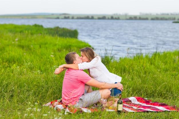 Jeune Couple Dans La Prairie D'été, Homme Et Femme Ayant Pique-nique Romantique. Photo Premium