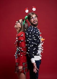 Jeune couple dans des vêtements de noël étranges attachés avec des lumières de noël
