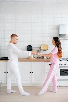 Jeune couple dansant dans la cuisine, jolie fille européenne aux cheveux longs en costume rose, cuisine blanche moderne