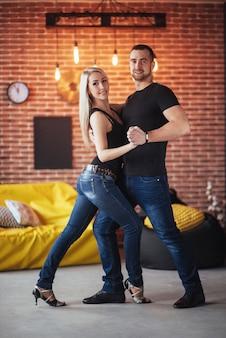 Jeune couple dansant des musiques latines: bachata, merengue, salsa. deux élégance pose sur un café avec des murs de briques
