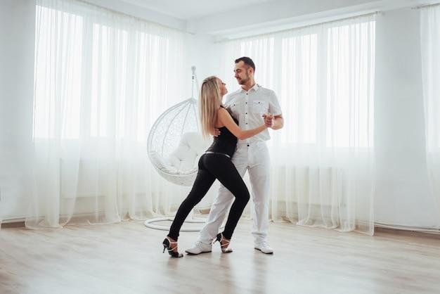 Jeune couple dansant des musiques latines: bachata, merengue, salsa. deux élégance pose sur la salle blanche