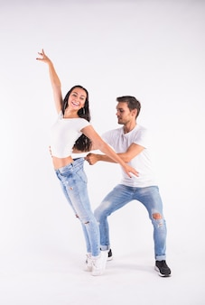 Jeune couple danse danse latine sociale bachata, merengue, salsa. deux élégance posent sur blanc