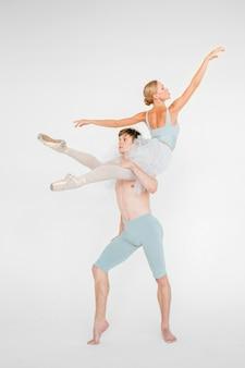 Jeune couple de danseurs de ballet moderne posant sur fond de studio blanc