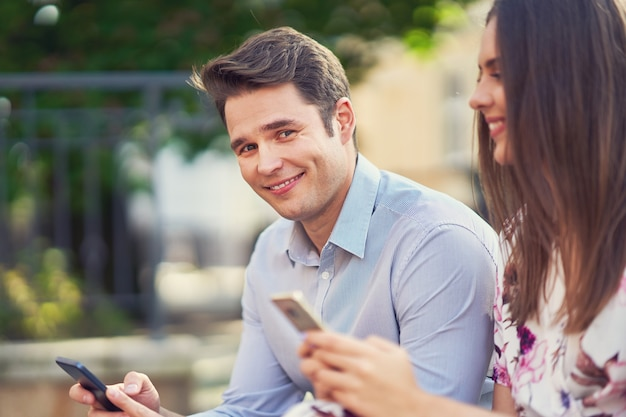Jeune couple datant dans le parc et utilisant des smartphones