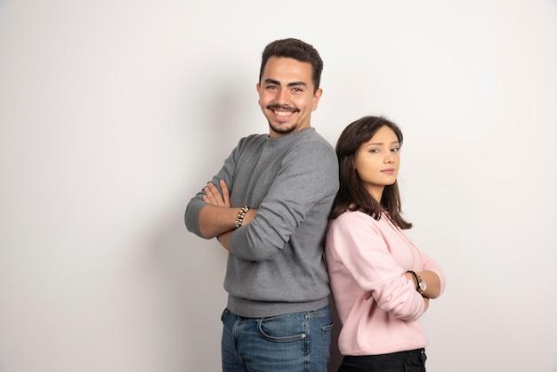 Jeune couple debout les bras croisés sur blanc.