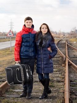 Jeune couple debout bras dessus bras dessous au milieu d'une voie ferrée rurale avec leurs bagages attendant l'arrivée du train pour commencer leur voyage