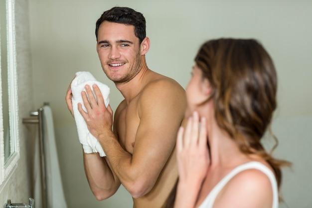 Jeune couple debout dans la salle de bain à la maison