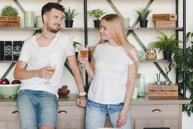 Jeune couple, debout, devant, étagère, tenue, verres, de, bière