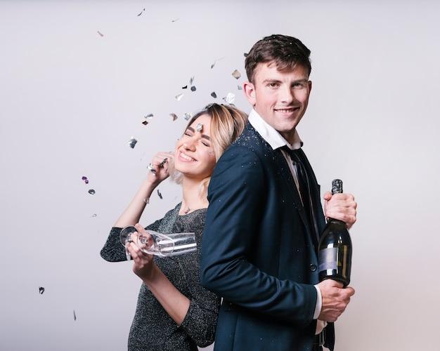 Jeune couple debout dos à dos sous les paillettes