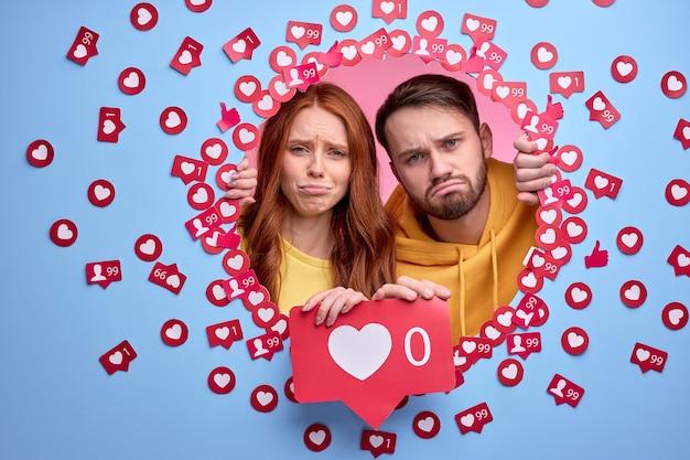 Jeune couple debout avec une expression faciale bouleversée n'ayant pas de taux et aime les signes sur les publications et les photos